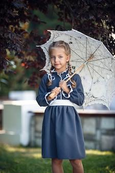 Urocza mała dziewczynka w sukience retro spaceru po mieście w słoneczny letni dzień. mała dziewczynka nosić mundurek szkolny.