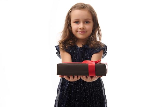 Urocza mała dziewczynka w wieczorowej granatowej sukience trzyma czarne pudełko z czerwoną wstążką na rękach i pokazuje to do kamery. rocznica, koncepcja czarny piątek. izolowane białe tło, kopia przestrzeń