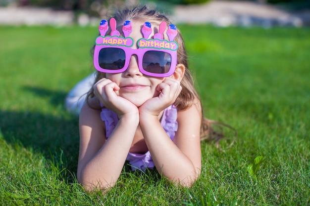 Urocza mała dziewczynka w wszystkiego najlepszego z okazji urodzin szkieł ono uśmiecha się plenerowy