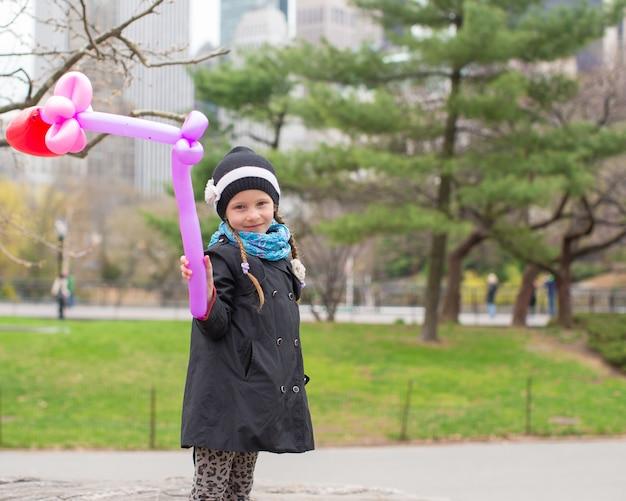 Urocza mała dziewczynka z balonem w central park przy miasto nowy jork