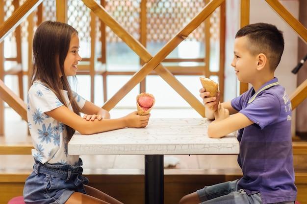 Urocza mała dziewczynka z bratem w kawiarni. jedzenie świeżych zimnych lodów.