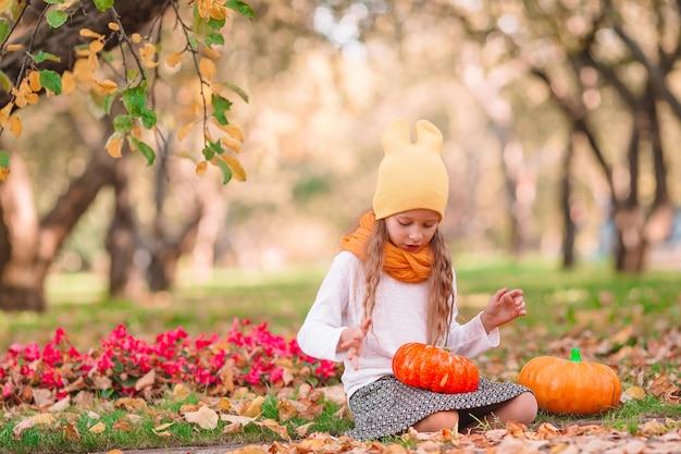 Urocza mała dziewczynka z dyni na zewnątrz w ciepły jesienny dzień. portret dziecka jesienią w październiku