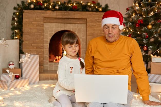 Urocza mała dziewczynka z dziadkiem siedzi i używa cyfrowego laptopa podczas wigilii, siedzi na podłodze na miękkiej karpie w pobliżu jodły i kominka, rodzina patrząc skoncentrowana na ekranie.