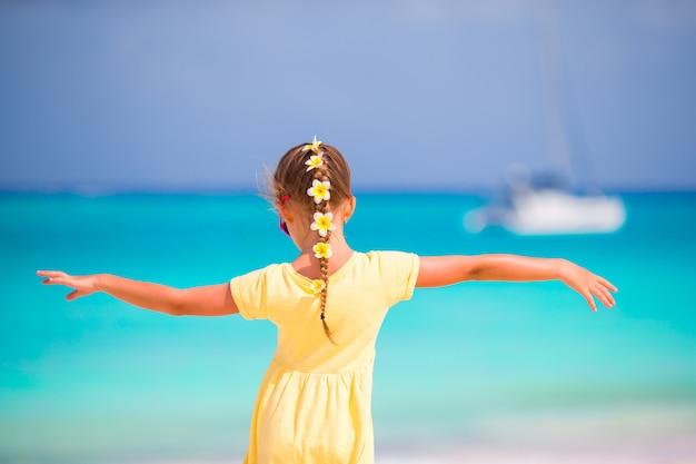 Urocza mała dziewczynka z frangipani kwitnie w włosy na plaży