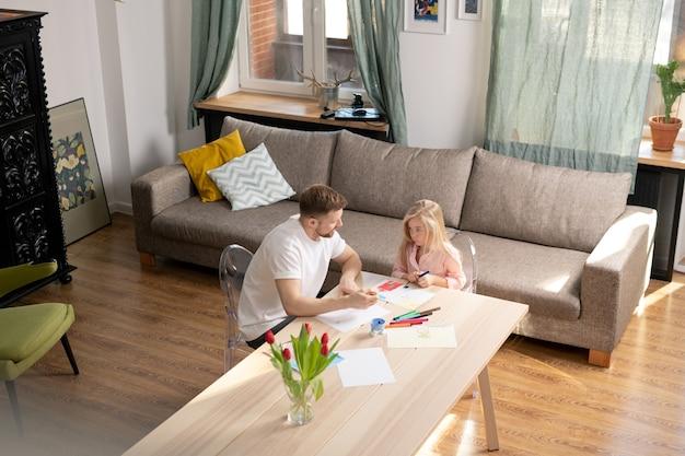 Urocza mała dziewczynka z kredką lub zakreślaczem patrzy na ojca i słucha go, siedząc przy stole i rysując w salonie