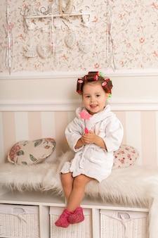 Urocza mała dziewczynka z lokami za pomocą lokówek. kopiuje zachowanie mamy. młoda fashionistka.