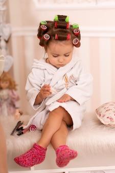 Urocza mała dziewczynka z lokówkami maluje paznokcie. kopiuje zachowanie mamy. młoda fashionistka. piękny dzień.
