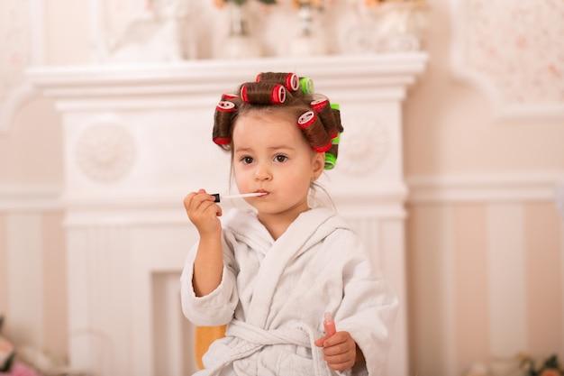 Urocza mała dziewczynka z matką w lokówek nakłada makijaż. mama uczy córkę stosowania kosmetyków. piękny dzień. dziewczyny to takie dziewczyny.