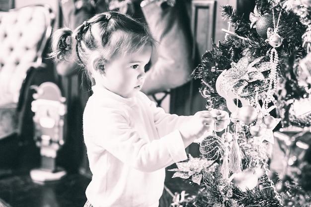 Urocza mała dziewczynka z ogonami w białym swetrze patrząc na pięknie udekorowaną choinkę
