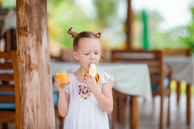 Urocza mała dziewczynka z świeżym sokiem pomarańczowym przy plenerową kawiarnią