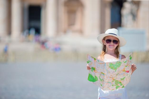 Urocza mała dziewczynka z turystyczną mapą