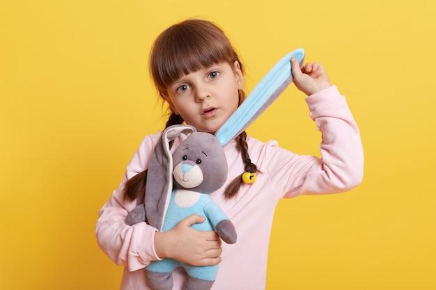 Urocza mała dziewczynka z zabawkami królika na białym tle na żółtym tle, dziecko ciągnące ucho królika i luźne w aparacie z zdziwionym i poważnym wyrazem twarzy.