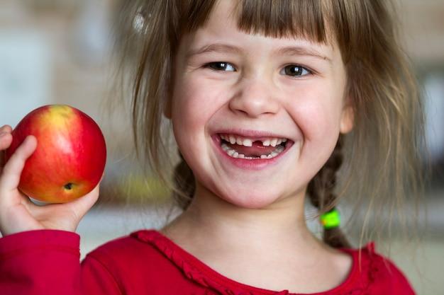 Urocza, mała, kręcona bezzębna dziewczyna uśmiecha się i trzyma czerwone jabłko. portret szczęśliwy dziecko je czerwonego jabłka. dziecko traci zęby mleczne. zdrowe odżywianie.