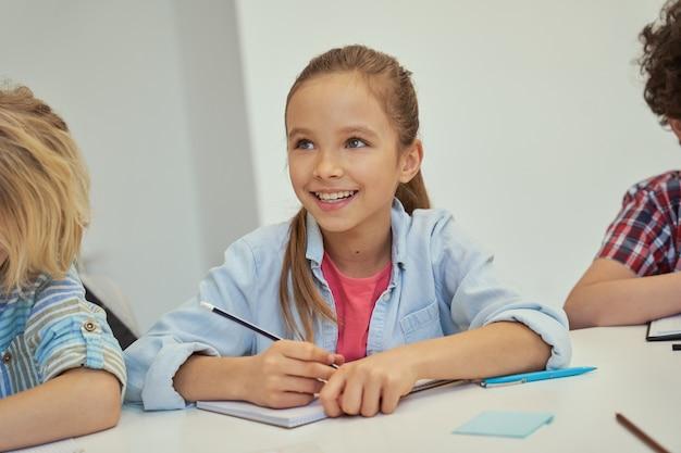 Urocza mała uczennica uśmiecha się trzymając ołówek i słuchając podczas nauki, siedząc w