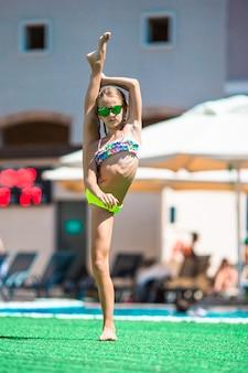 Urocza małej dziewczynki dopłynięcie przy plenerowym pływackim basenem