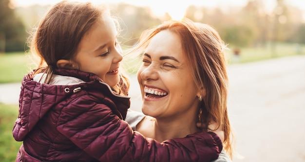 Urocza mama i jej mała dziewczynka śmiejąca się podczas letniego spaceru