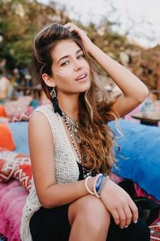 Urocza marzycielska dziewczyna pozuje ręką w górze, siedząc na kanapie w kawiarni na świeżym powietrzu w godzinach porannych