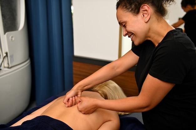 Urocza masażystka rozmawia z klientką podczas masażu pleców w salonie spa. indywidualne podejście do klienta. przyjazny personel w salonach spa