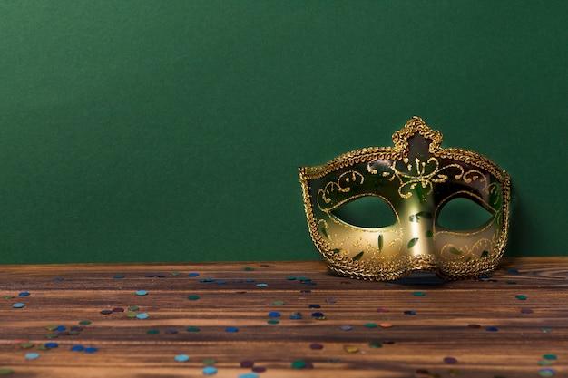Urocza maska w pobliżu zielonej ściany