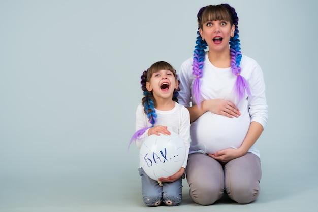 Urocza matka w ciąży i zabawna córka pozytywne śmieszne rodziny z piłką na niebieskiej ścianie w oczekiwaniu na małego noworodka. copyspace