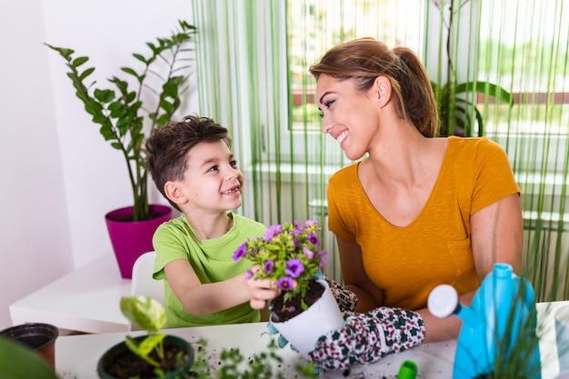 Urocza matka z chłopcem dbającymi o kwiatek w doniczce i zestawie ogrodniczym. dbaj o roślinę doniczkową