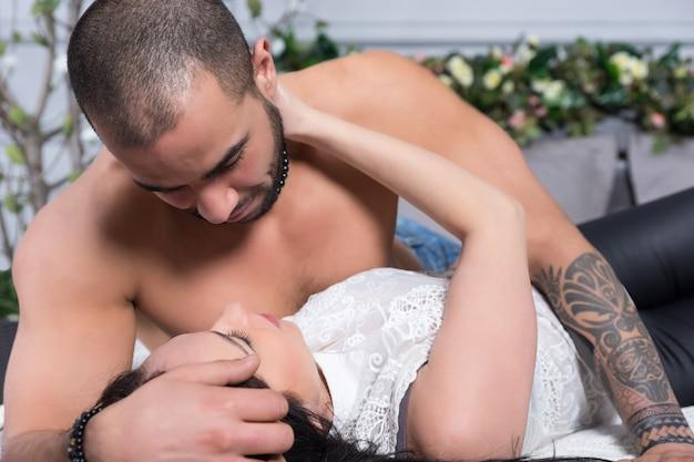 Urocza międzynarodowa para mężczyzn z nagą klatką piersiową, wytatuowanymi rękami i brunetką patrzą na siebie, leżąc na szarym, wygodnym łóżku w sypialni