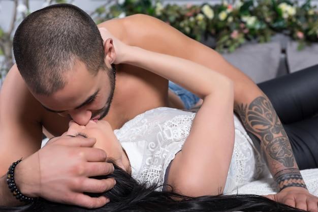 Urocza międzynarodowa para mężczyzn z nagą klatką piersiową, wytatuowanymi rękami i całującą brunetką leżącą na szarym, wygodnym łóżku w sypialni
