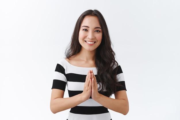 Urocza miła kobieta z azji wschodniej w pasiastym t-shircie trzyma ręce w modlitwie, dłonie splecione przy piersiach, szeroko uśmiechnięta, dziękuje za przysługę, wdzięczna za pomoc, stoi zachwycona białym tłem