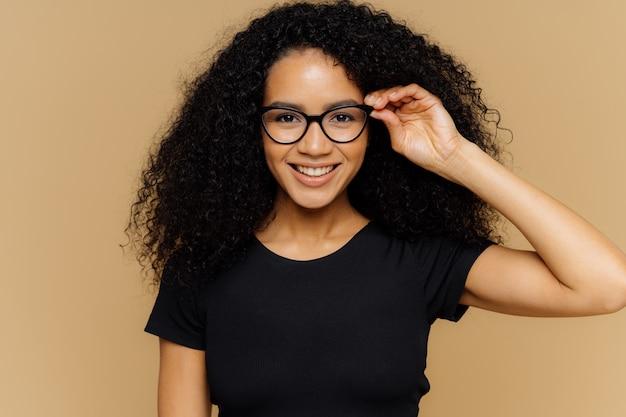 Urocza młoda afroamerykanka uśmiecha się do kamery, trzyma rękę na brzegu okularów
