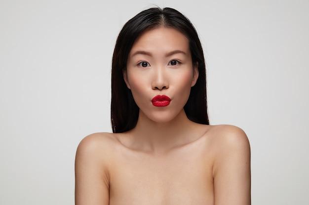 Urocza młoda atrakcyjna brunetka dama z świątecznym makijażem składająca usta w pocałunek i trzymając ręce w dół, stojąc nad białą ścianą