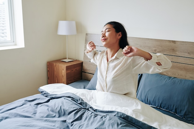 Urocza młoda azjatka rozciągająca się w łóżku po przebudzeniu w niedzielny poranek