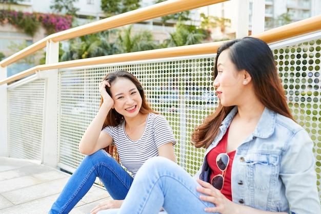 Urocza młoda azjatka spędza czas ze swoją przyjaciółką siedzącą na moście i omawiającą wiadomości