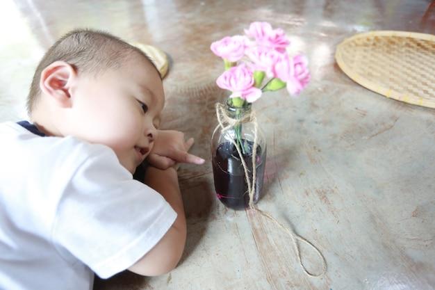 Urocza młoda azjatycka chłopiec robi bukietowi kwiatów w domu.