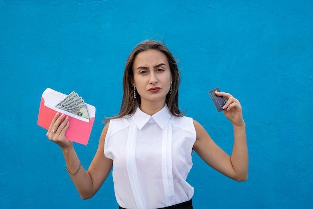 Urocza młoda biznesowa dama trzymająca dolary w kopercie i kartę kredytową na zakupy