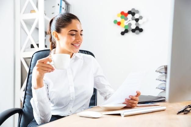 Urocza młoda bizneswoman czyta raport i trzyma filiżankę kawy siedząc przy biurku