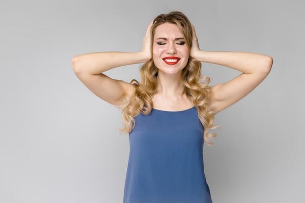 Urocza młoda blondynka ma dość dziewczyny w niebieskich ubraniach, zamykając uszy rękami na szaro