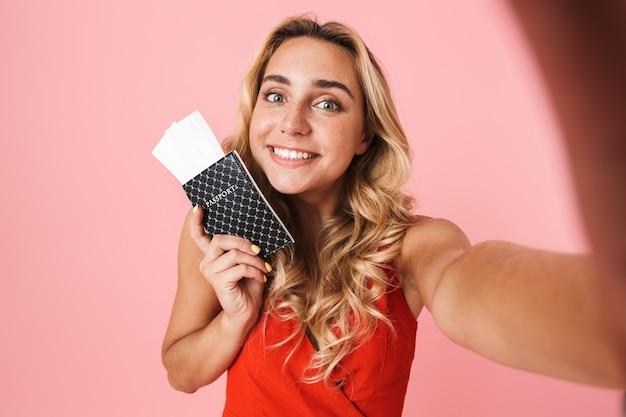 Urocza młoda blondynka w letniej sukience, stojąca na białym tle nad różową ścianą, robiąca selfie, pokazująca paszport z biletami lotniczymi