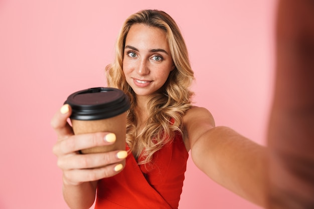 Urocza młoda blondynka w letniej sukience, stojąca na białym tle nad różową ścianą, robiąca selfie, trzymająca filiżankę na wynos