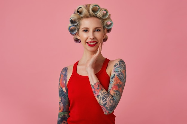 Urocza młoda blondynka wytatuowana kobieta z wieczorowym makijażem, robiąca fryzurę przed nadchodzącą imprezą, dotykająca miękkiej twarzy i uśmiechająca się delikatnie do kamery, odizolowana na różowym tle