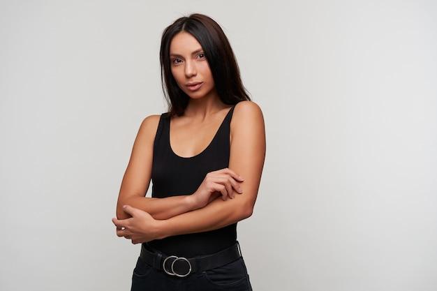Urocza młoda brązowooka brunetka dama składająca ręce na piersi ze spokojną twarzą, ubrana w swobodne czarne ubrania podczas pozowania na biało