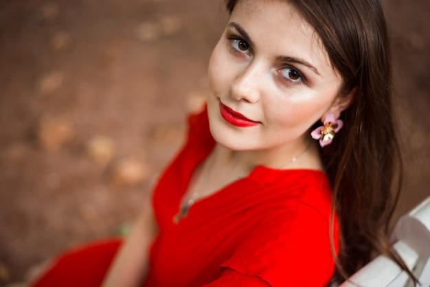 Urocza młoda brunetka dziewczyna w czerwonej sukience siedzi na ławce w parku