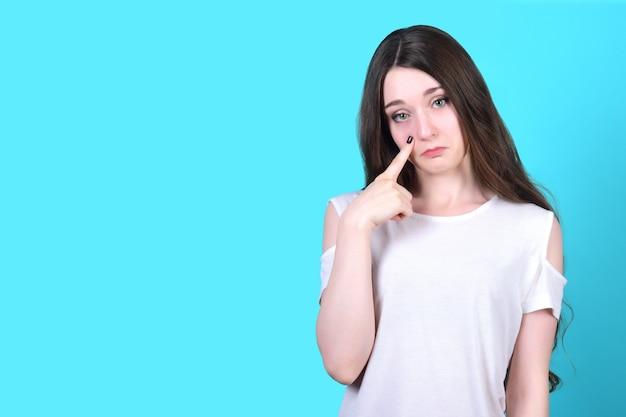 Urocza młoda brunetka jest zdenerwowana, a na jej palcu widać łzę na policzku.