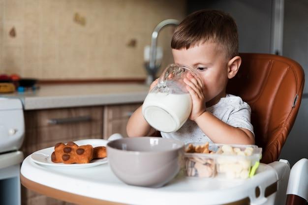 Urocza młoda chłopiec pije mleko