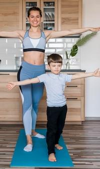 Urocza młoda chłopiec trenuje wraz z matką