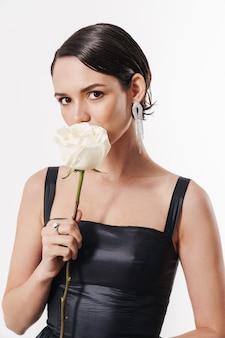 Urocza młoda czarująca ładna kobieta trzymająca kwiat i patrząca na kamerę odizolowaną nad białą ścianą