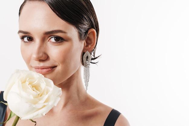 Urocza młoda czarująca ładna kobieta uśmiechająca się i trzymająca biały kwiat na białym tle nad białą ścianą