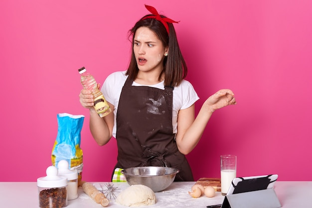 Urocza młoda dama robi piekarnię w kuchni, używa wielu składników i przyborów do wyrabiania ciasta, ze zdumieniem spogląda na butelkę oleju, używa tabletu do przygotowywania nowych przepisów. skopiuj miejsce