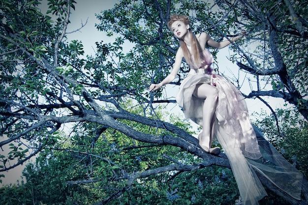 Urocza młoda dama ubrana w elegancką białą sukienkę z różami stojącą na drzewie w drewnie
