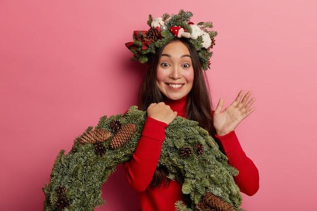 Urocza młoda dama uśmiecha się przyjemnie w świątecznym wieńcu na głowie
