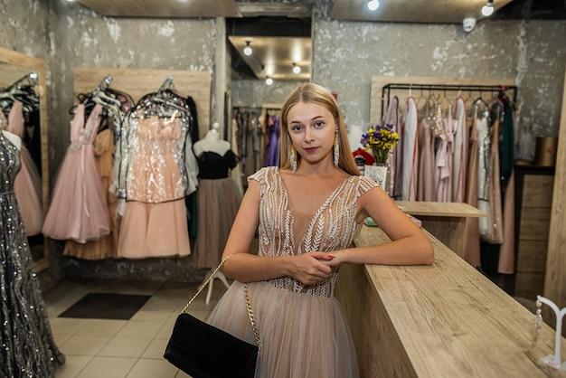Urocza młoda dama wybrała idealną suknię wieczorową w sklepie odzieżowym i pozuje do niej. koncepcja zakupów